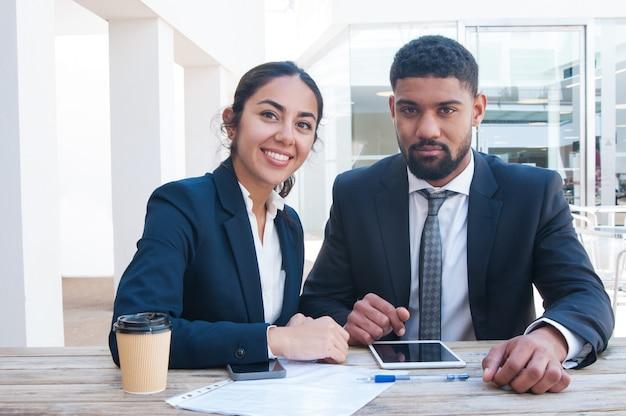 Współpracownicy pracuje przy biurowym biurkiem z pastylką, papierami i kawą