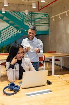 Współpracownicy rozmawiają o pracy przy czarnej kawie