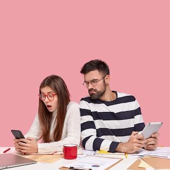 Współpracownicy siedzący przy biurku z dokumentami i gadżetami