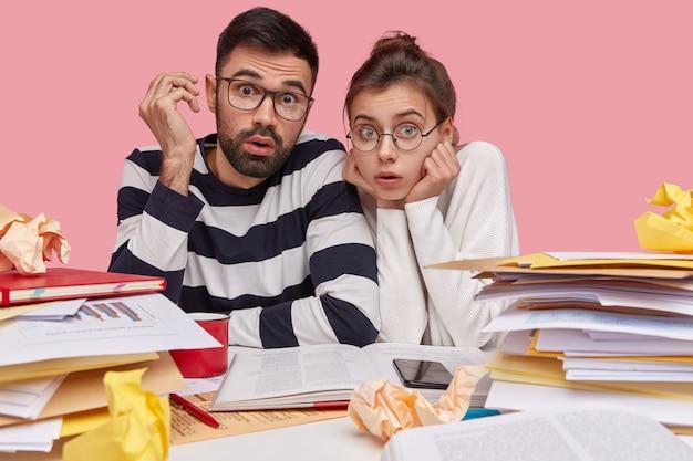 Współpracownicy siedzący przy biurku z dokumentami