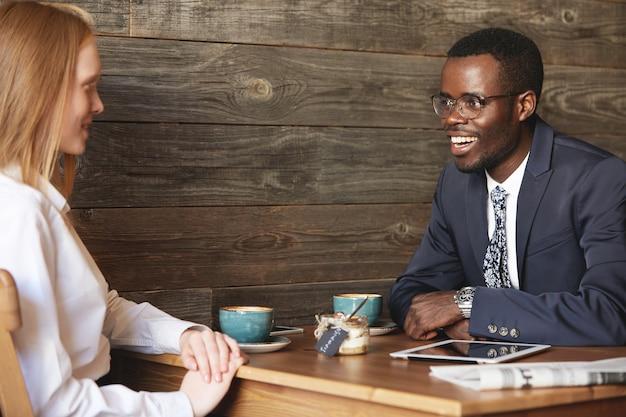 Współpracownicy siedzący w kawiarni ubrani formalnie