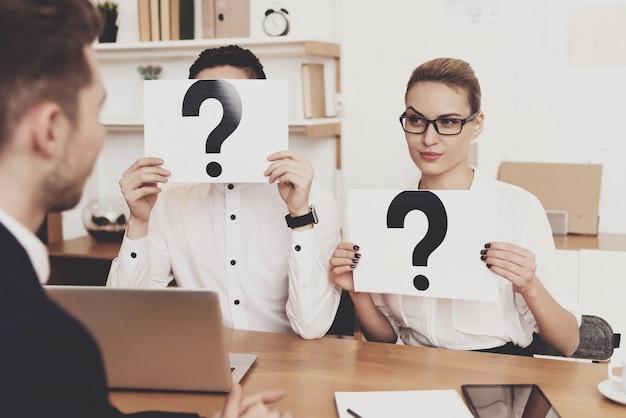 Współpracownicy trzymają znaki zapytania podczas rozmowy kwalifikacyjnej.