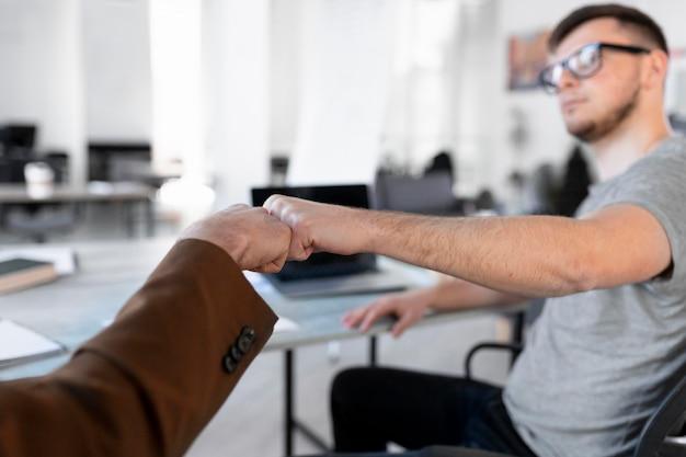 Współpracownicy uderzają pięścią w biuro