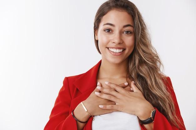 Współpracownicy urządzają przyjęcie, gratulując kobiecie osiągnięć. portret zaskoczony wdzięczny zadowolony szczęśliwa młoda atrakcyjna kobieta naciskająca dłonie w klatce piersiowej wdzięczna uśmiechnięta optymistyczna, biała ściana