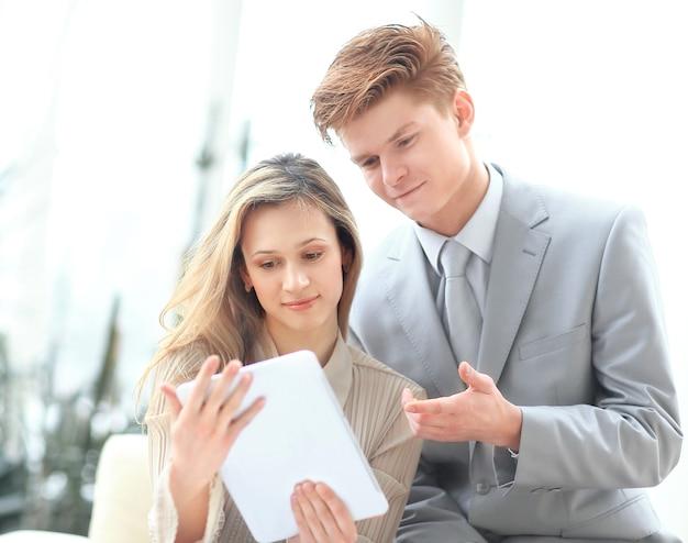 Współpracownicy używają cyfrowego tabletu, aby uzyskać niezbędne informacje.
