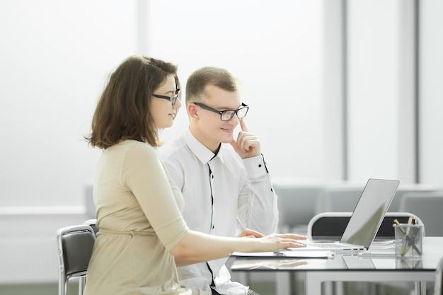 Współpracownicy używają laptopa do pracy w biurze
