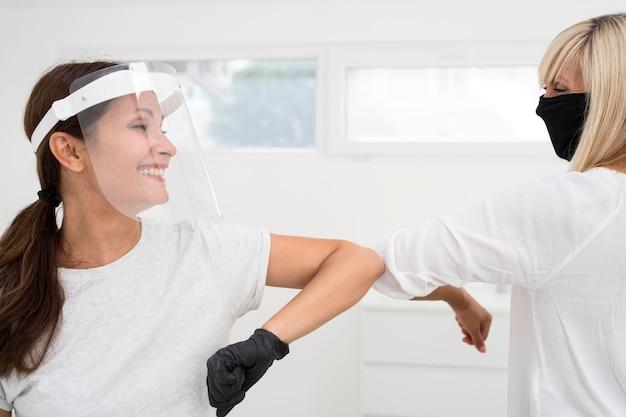 Współpracownicy używający alternatywnego powitania z uderzeniem łokcia