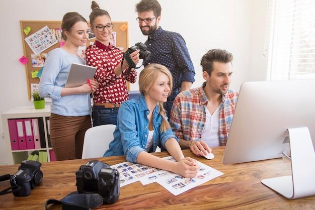Współpracownicy w biurze z aparatami fotograficznymi i komputerem
