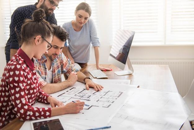Współpracownicy W Biurze Z Planami Architektonicznymi I Komputerem Darmowe Zdjęcia