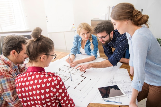Współpracownicy w biurze z planami architektonicznymi i komputerem