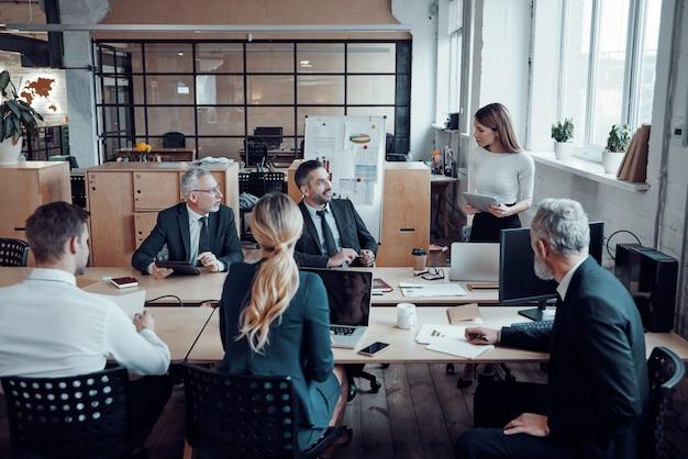 Współpracownicy w eleganckich strojach wizytowych omawiają świeże pomysły biznesowe podczas pracy w nowoczesnym biurze
