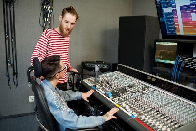 Współpracownicy w nowoczesnym studiu dźwiękowym
