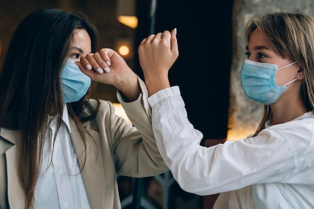 Współpracownicy w ochronnych maskach przybijają piątkę na łokciach