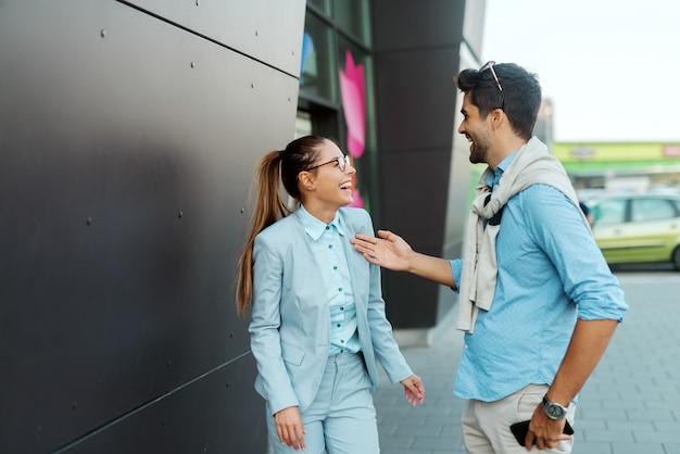 Współpracownicy wychodzą z pracy i śmieją się podczas spaceru po ulicy. kobieta trzyma dokumenty, podczas gdy mężczyzna trzyma tablet.
