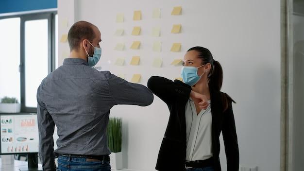 Współpracownicy z maseczką dotykają łokcia ze swoim kolegą, aby zapobiec zakażeniu koronawirusem. współpracownicy szanujący dystans społeczny podczas pracy nad firmowym projektem komunikacyjnym