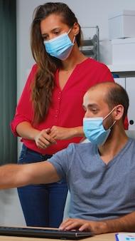 Współpracownicy z ochronnymi maskami na twarz pracujący razem w miejscu pracy podczas pandemii. zespół w nowym normalnym biurze w osobistej firmie korporacyjnej, pisząc na klawiaturze komputera, patrząc na pulpit