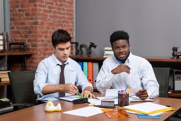 Współpracownicy z procesu pracy z widokiem z przodu prowadzący negocjacje biznesowe w biurze