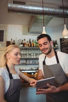 Współpracownicy za pomocą cyfrowego tabletu w kawiarni