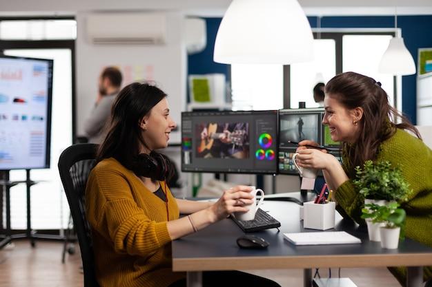 Współpracownicy zajmujący się montażem wideo dyskutujący przed komputerem pracującym dla materiału filmowego dla klienta