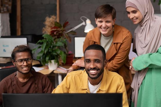Współpracownicy ze średnim strzałem patrzący na komputer