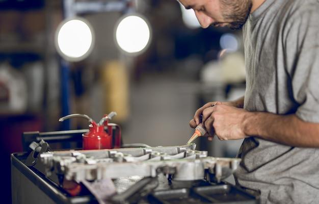 Współpracownik, który dodaje olej do silnika samochodu