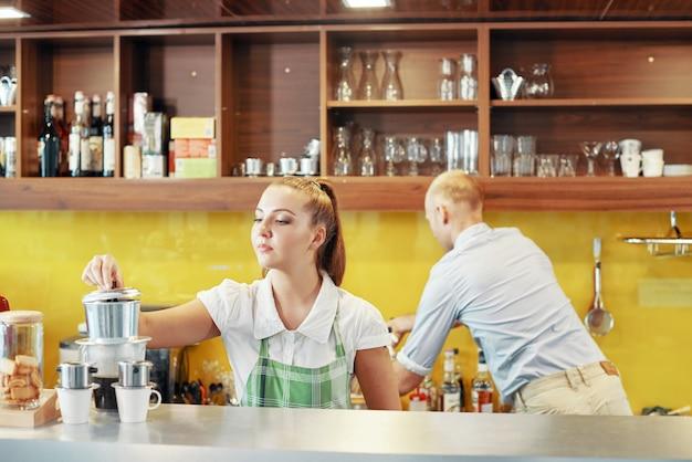Współpracujący barista i manager w kasie