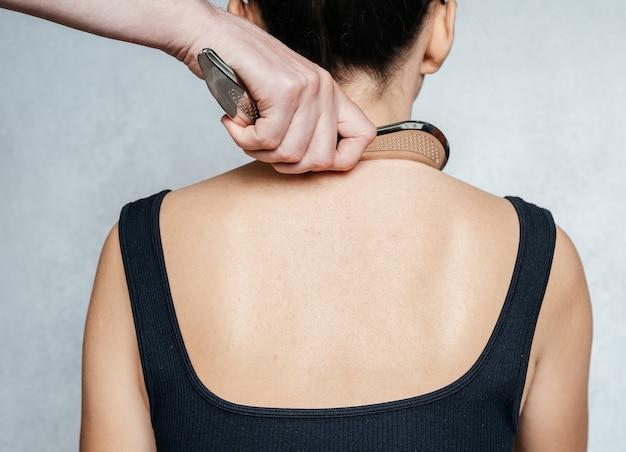 Wspomagana instrumentalnie mobilizacja tkanek miękkich kobieta po leczeniu tkanek miękkich na plecach z...