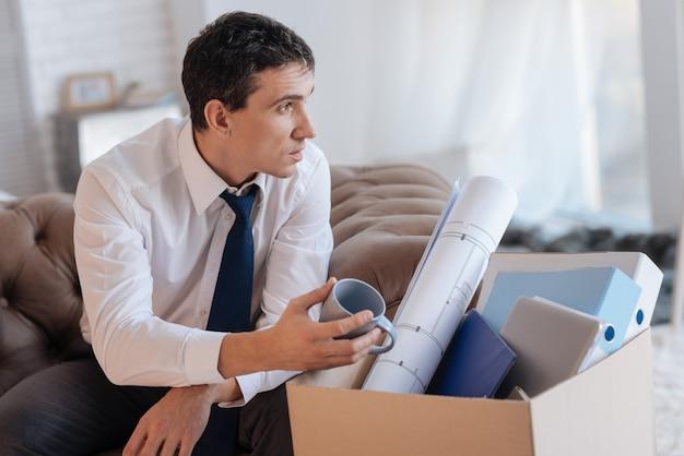 Wspomnienia. elegancki zbędny spokojny mężczyzna z zamyśleniem spoglądający w dal, siedząc ze swoim ulubionym kubkiem z pudełkiem rzeczy osobistych u boku
