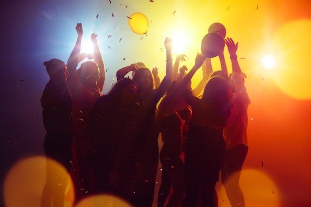 Wspomnienia. tłum ludzi w sylwetce podnosi ręce na parkiecie na neonowym tle. życie nocne, klub, muzyka, taniec, ruch, młodzież. żółto-niebieskie kolory i poruszające dziewczyny i chłopcy.