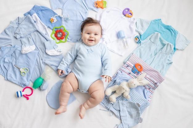 Wśród dziecięcych akcesoriów i ubranek leży niemowlę w niebieskim ubranku