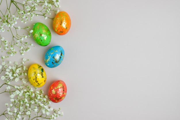 Wśród kwiatów są kolorowe jajka. minimalna koncepcja wielkanocy. wielkanocny baner, kartka z życzeniami, tło