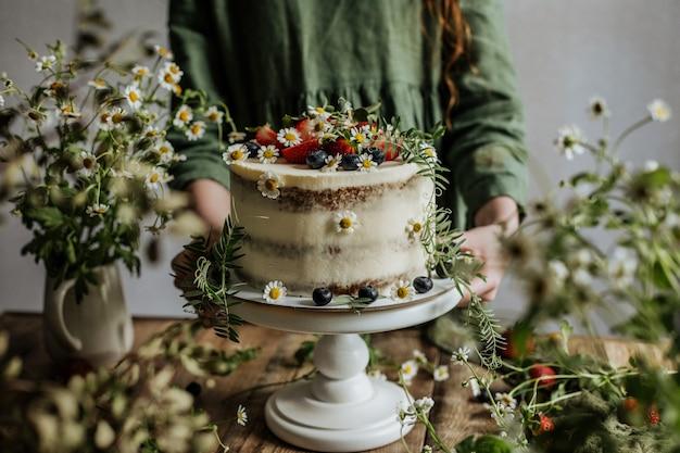 Wśród zieleni stoi piękny letni tort ozdobiony jagodami i kwiatami