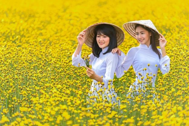 Wśród żółtych kwiatów stała kobieta w starożytnym wietnamskim stroju narodowym, trzymająca kapelusz wykonany z wikliny