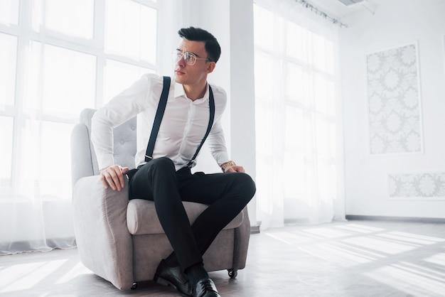 Wstawaj, nadchodzą nowe oferty. zdjęcie atrakcyjnego faceta w okularach i stylowym nosić siedząc na krześle.
