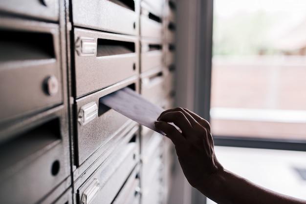 Wstawianie listu do metalowej skrzynki pocztowej budynku, zbliżenie.