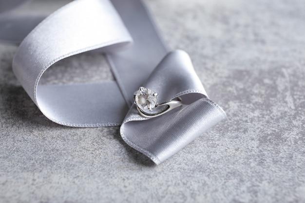 Wstążka z pięknym pierścionkiem zaręczynowym na stole