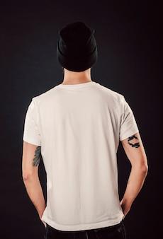 Wsteczne ujęcie przystojnego brodatego mężczyzny ze świeżą fryzurą i wytatuowanymi ramionami pozujące na makiecie odizolowanej ściany w białej prostej pustej koszulce gotowej do projektów