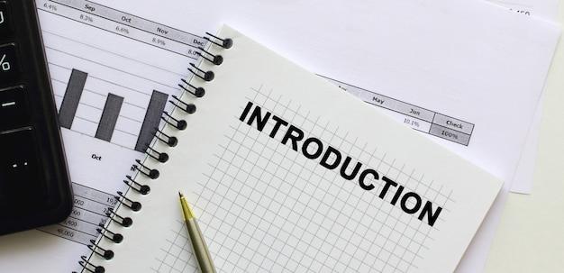 Wstęp tekstowy na stronie notatnika leżącego na wykresach finansowych na biurku. w pobliżu kalkulatora. pomysł na biznes.