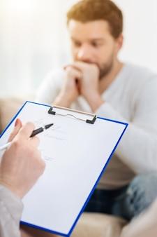 Wstępna diagnoza. zbliżenie na notatki psychologa ze wstępną diagnozą zapisywaną podczas sesji fizjologicznej z pacjentem