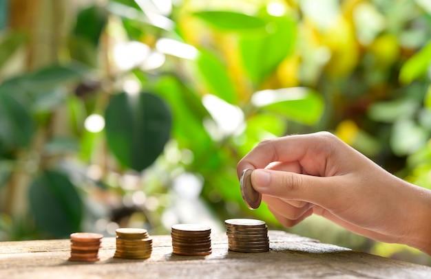 Wstępne oszczędzanie pieniędzy. kobieca ręka stos monet do pokazanej koncepcji rozwijania biznesu i zamożności.