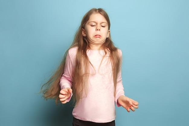 Wstręt. wrażliwa dziewczyna nastolatka na niebieskim tle studia. wyraz twarzy i koncepcja emocji ludzi. modne kolory. przedni widok. portret do połowy długości