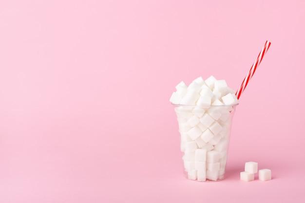 Wstrząsnąć szklanką pełną kostek cukru na pastelowym różowym tle. koncepcja niezdrowej żywności. skopiuj miejsce, widok z boku.