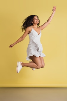 Wstrząśnięty. afro-portret pięknej kobiety na białym tle na żółtej ścianie z copyspace. stylowa modelka. pojęcie ludzkich emocji, wyrazu twarzy, sprzedaży, reklamy, mody, młodzieży.