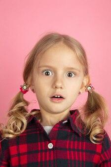 Wstrząśnięty. kaukaski dziewczynki z bliska portret na różowej ścianie. piękna modelka z blond włosami.