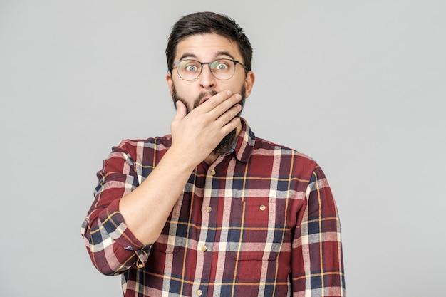 Wstrząśnięty podekscytowany facet w okularach izolowanych na szaro