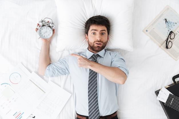 Wstrząśnięty przystojny młody biznesmen rano w łóżku leży śpiąca trzymając budzik