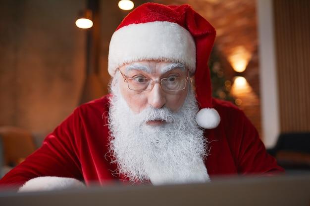 Wstrząśnięty, przystojny święty mikołaj z białą brodą, korzystający z laptopa podczas czytania wiadomości internetowych