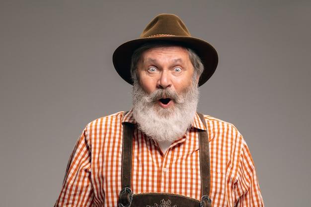 Wstrząśnięty. szczęśliwy starszy mężczyzna ubrany w tradycyjny austriacki lub bawarski strój, wskazując na szarym tle studio. miejsce. obchody, oktoberfest, festiwal, koncepcja tradycji.
