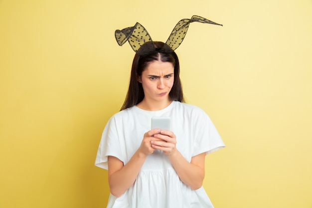 Wstrząśnięty telefonem. kaukaski kobieta jako zajączek na żółtym tle.