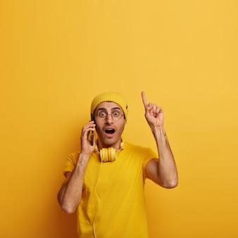 Wstrząśnięty zatroskany młody człowiek zaskoczony kłopotliwymi wiadomościami, wskazuje palcem wyżej, nosi okulary i żółty strój